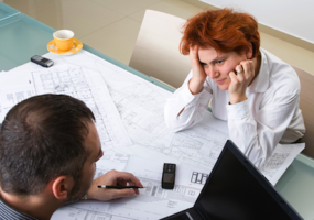 A builder and a client sitting at a table reviewing blueprints