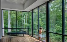 Girl looking into the woods from  floor to ceiling windows